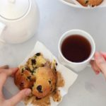 Birds eye view of someone breaking into a blueberry muffin with a tea cup and teapot beside it.