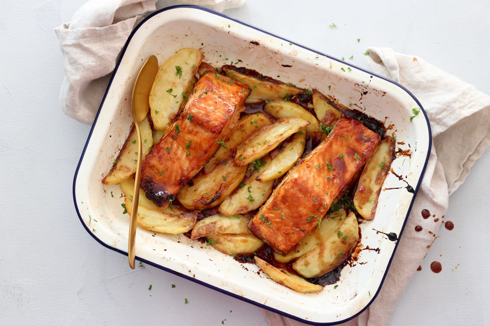 Top down image of Asian glazed salmon on a bed of crispy wedges in a baking tray with a serving spoon and tea towel