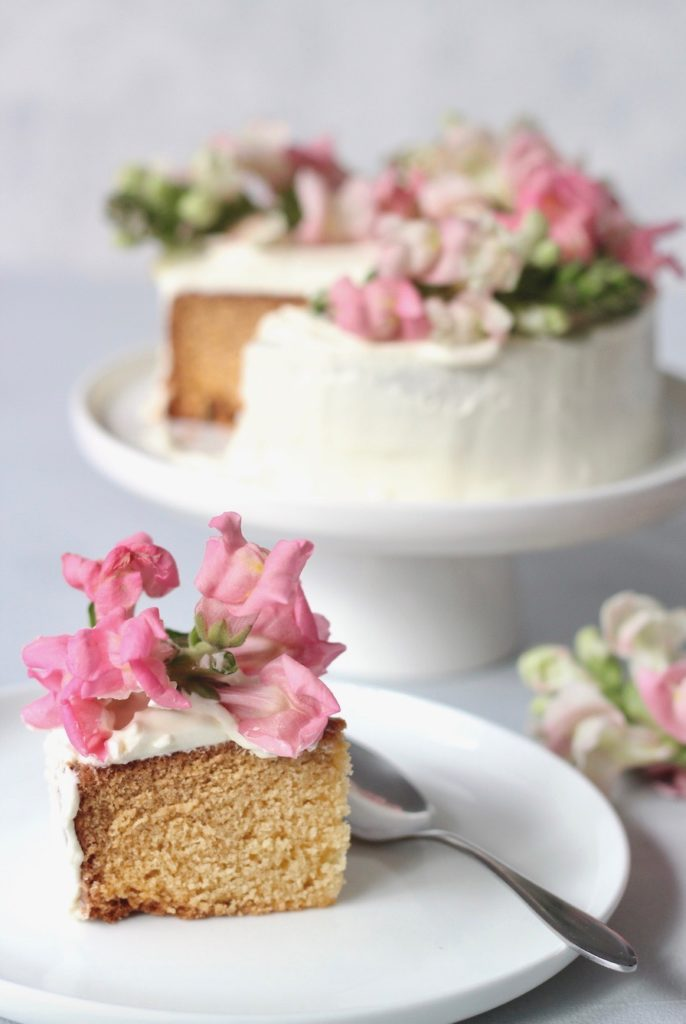 A slice of vanilla butter cake topped with pink flowers on a plate with a teaspoon and the sliced cake on a stand in the background