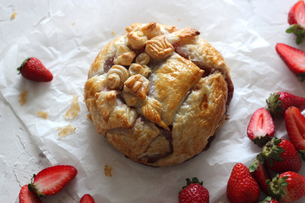 Puff pastry parcel with scattered strawberries.